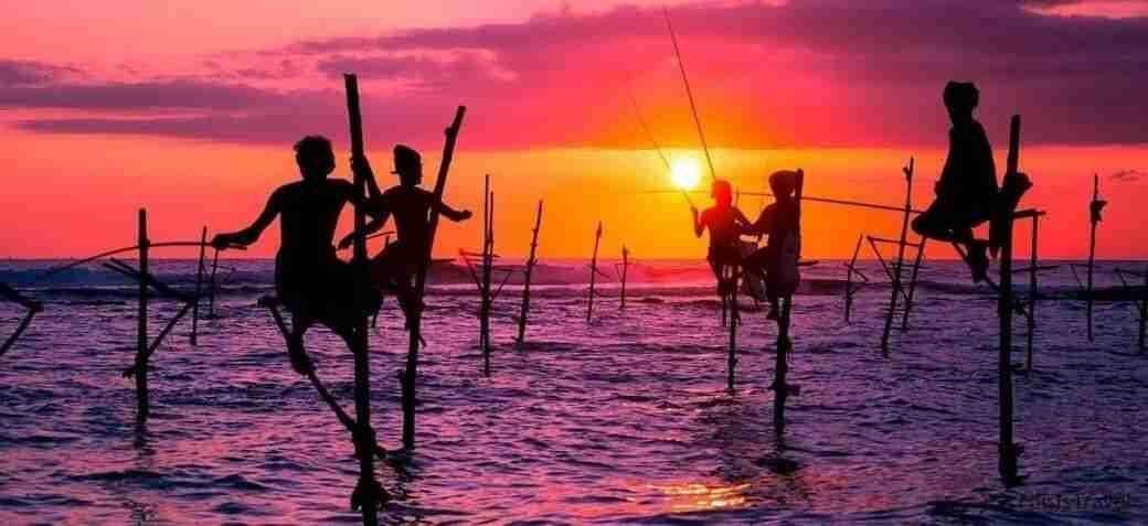 Pescadores tipicos de sri lanka sobre el mar con palos
