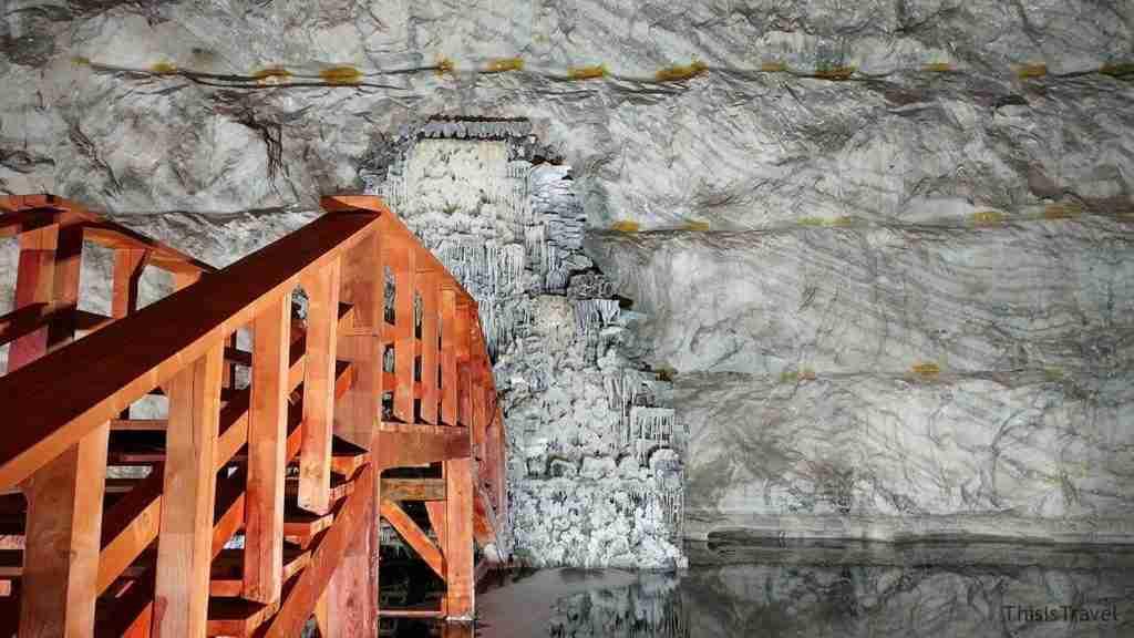 en el interior de la mina Slanic, nacimiento de agua, sal en estalactitas,  un puente y lago.