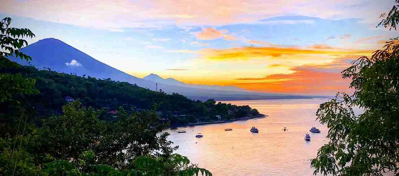 hermosa puesta de sol en Amed, Bali con el volcan Amung a lo lejos y sus tonos rojizos marinos